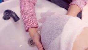 O cabelo do cliente da lavagem do barbeiro no sal?o de beleza no dissipador filme