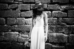 O cabelo esconde a cara da senhora quando estiver atrás de uma parede de pedra Foto de Stock