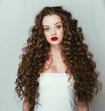 O cabelo longo do retrato da mulher do cabelo encaracolado com perfeito compõe os bordos vermelhos fotografia de stock royalty free