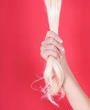 O cabelo louro na f?mea cede o vermelho Fotografia de Stock Royalty Free
