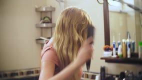 O cabelo perdedor da mulher, uma mulher loura com cabelo longo é penteado no banheiro na frente do espelho o cabelo permanece no video estoque