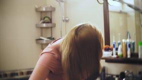 O cabelo perdedor da mulher, uma mulher loura com cabelo longo é penteado no banheiro na frente do espelho o cabelo permanece no filme