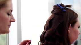O cabelo que denomina o cabelo, o cabeleireiro faz um permanente no salão de beleza com a ajuda do cabelo e do pulverizador de ca filme