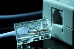 O cabo azul do Internet da rede do cabo de remendo do twisted pair em tons azuis em um fundo preto é introduzido no conector da r Foto de Stock Royalty Free