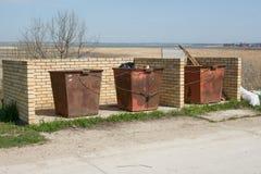 O cabo ligado tanque do metal do lixo três está no lugar designado e é encerrado pelo tijolo imagem de stock