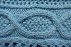 O cabo trança o teste padrão na tela feita malha azul foto de stock