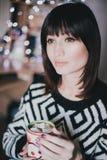 O cacau da bebida da mulher com os marshmallows na frente do xmas ilumina-se Fotos de Stock