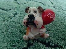 O cachorrinho bonito ama-o que senta-se no fundo verde Imagem de Stock Royalty Free