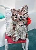 O cachorrinho cerâmico engraçado com uma flor que senta-se em uma cadeira Fotos de Stock