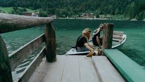 O cachorrinho parvo e bonito salta do barco para suportar video estoque