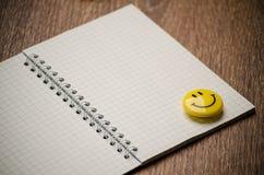 O caderno aberto com páginas vazias e o ícone sorriem Foto de Stock