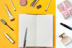 O caderno aberto, para fazer a lista, compõe artigos, perfume e caixa de presente no fundo pastel, vista superior Imagem de Stock Royalty Free