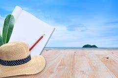O caderno com o chapéu do lápis e de palha no assoalho de madeira com natureza do mar ajardina Imagem de Stock