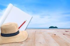 O caderno com o chapéu do lápis e de palha no assoalho de madeira com natureza do mar ajardina Imagens de Stock