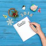 O caderno com OBJETIVOS text e a pena de terra arrendada da mão do ` s do homem acima com números ornamento de 2018 e do ano novo Foto de Stock Royalty Free
