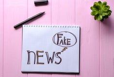 O caderno com palavras FALSIFICA NOTÍCIAS no fundo de madeira foto de stock royalty free
