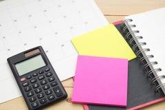 O caderno da vista superior, a calculadora, a nota de post-it e o calendário puseram sobre w Imagem de Stock