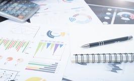 O caderno e o original representam graficamente financeiro com a calculadora na mesa Imagens de Stock Royalty Free