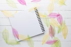 O caderno espiral com cor secou as folhas na madeira branca Imagens de Stock
