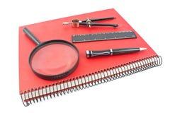 O caderno espiral vermelho com compasso, régua e lente de aumento de desenho é Imagens de Stock Royalty Free
