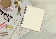 O caderno, os acessórios dourados do escritório, a xícara de café, as linhas, os vidros na tabela do granito e o assoalho branco imagem de stock