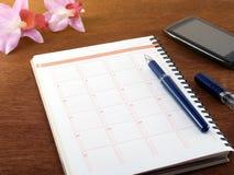 O caderno, a pena, o smartphone preto e as orquídeas artificiais roxas florescem no assoalho de madeira da tabela do marrom escur Foto de Stock