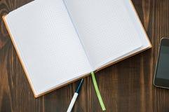 O caderno, telefone, pena coloca no assoalho fotos de stock royalty free