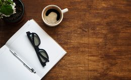 O caderno vazio com vidros pretos, a pena e a xícara de café são sobre a tabela de madeira Configuração lisa imagem de stock royalty free