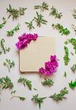O caderno vazio decorou flores roxas em um fundo branco, vista superior Bloco de notas decorado com folhas e violeta verdes Confi imagens de stock royalty free