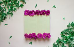 O caderno vazio decorou flores roxas em um fundo branco, vista superior Bloco de notas decorado com folhas e violeta verdes Confi ilustração stock