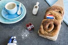 O café da manhã com rolo de pão holandês tradicional da canela, chamou Taça imagens de stock royalty free