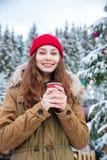 O café bebendo da mulher próximo decorou a árvore de Natal na floresta do inverno imagens de stock
