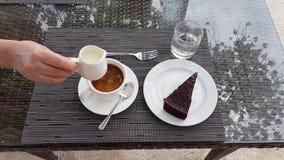 O café, o bolo e a água serviram na tabela Mão fêmea que derrama no leite Alimento e conceito da bebida Fundos bonitos vídeos de arquivo