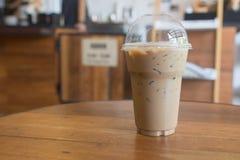 O café congelado leva embora dentro o vidro plástico do copo na tabela de madeira mim Fotos de Stock
