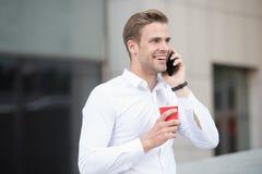 O café da bebida do homem fala o fundo urbano do telefone Café da bebida Cada sorvo é momento do cuidado do auto Empresários das  foto de stock