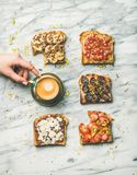 O café da manhã saudável com brindes e ` wholegrain s da mulher entrega a tomada do café Fotografia de Stock