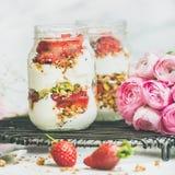 O café da manhã saudável da mola range com as flores cor-de-rosa do raninkulus, comer limpo imagem de stock