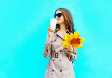 O café das bebidas da mulher da forma do copo guarda as folhas de bordo amarelas do outono Fotografia de Stock Royalty Free