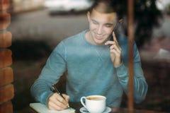O café de trabalho e bebendo do homem de negócio em um café e escreve para baixo algo no caderno Imagens de Stock