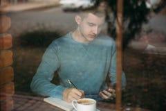 O café de trabalho e bebendo do homem de negócio em um café e escreve para baixo algo no caderno Imagem de Stock Royalty Free