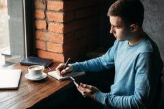 O café de trabalho e bebendo do homem de negócio em um café e escreve para baixo algo no caderno Imagens de Stock Royalty Free