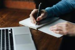 O café de trabalho e bebendo do homem de negócio em um café e escreve para baixo algo no caderno Foto de Stock