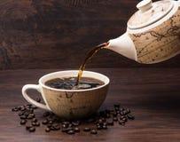 O café derrama no copo de Coffe com o potenciômetro de Coffe com feijões de café fotografia de stock royalty free