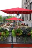 O café exterior é protegido por guarda-chuvas vermelhos foto de stock