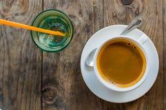 O café forte e escuro em um copo branco da porcelana serviu com um vidro da água em um lado em uma tabela de madeira fora foto de stock