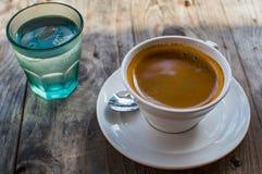 O café forte e escuro em um copo branco da porcelana serviu com um vidro da água em um lado em uma tabela de madeira fora fotografia de stock royalty free