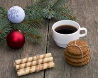 O café, o ligamento dois das cookies e um ramo conífero com scen Imagens de Stock