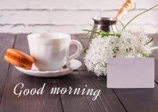 O café, os macarons em uns pires e um ramalhete das flores com um cartão a inscrição são um bom dia Foto de Stock