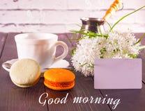 O café, os macarons em uns pires e um ramalhete das flores com um cartão a inscrição são um bom dia Imagem de Stock