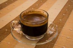 O café, pôs sobre o fundo marrom do algodão Fotografia de Stock Royalty Free